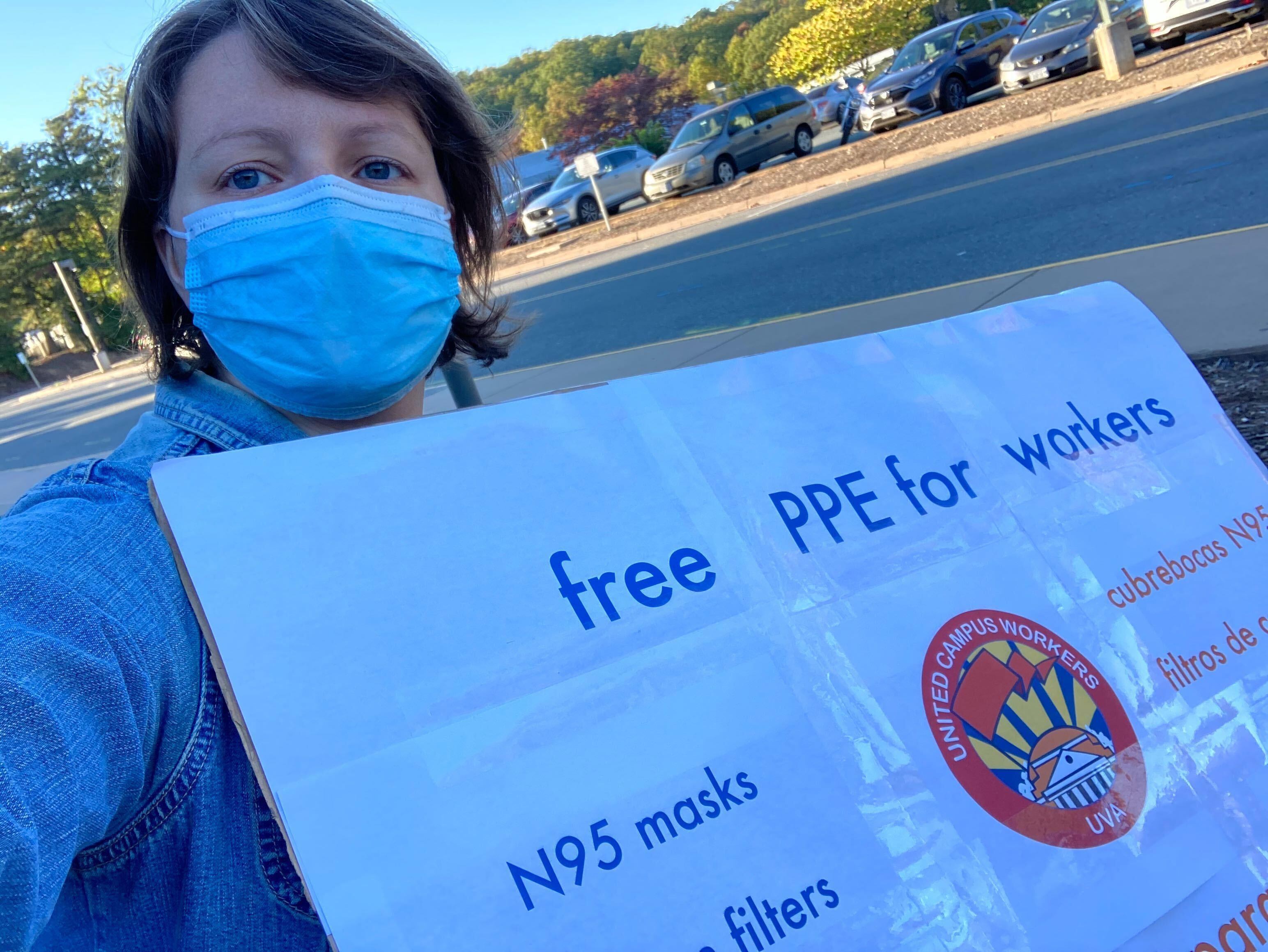 "UCWVA-UVA member holds sign outside in Charlottesville for our mutual aid drive, saying ""free ppe for workers. N95 Masks. Filters. Cubrebacas N95. Filtros..."""