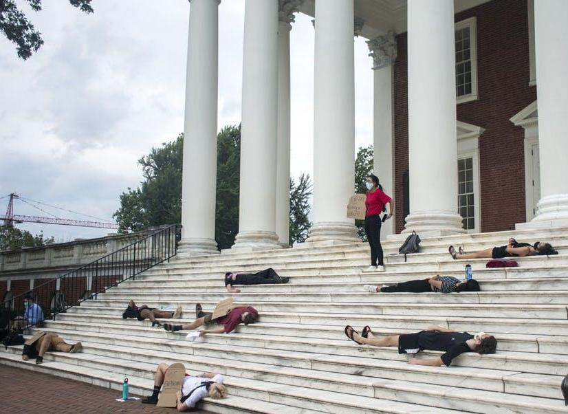 Photo from the Cavalier Daily of UCWVA Die In Protest September 2020. UCWVA members lie as if dead on UVA rotunda steps. One UCWVA members stands at top of stairs. All hold gravestone shaped placards with anti-austerity messages.